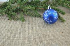 Blå Chirstmas prydnad och ett sörjaträd arkivfoto