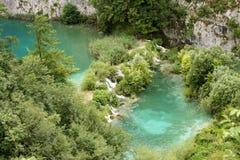 Blå crystal ren sjö med fiskar och vattenfall Arkivfoto