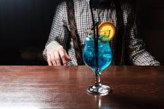 Blå curacao coctail med limefrukt, is och mintkaramellen i martini exponeringsglas på träbakgrund royaltyfri bild