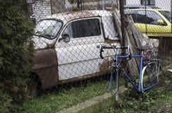 Blå cykel, var hjul tas bort, och en gammal rostig bil bak ett staket Arkivfoton
