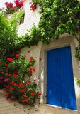 Blå dörr med blommor i medelhavs- grekisk by Royaltyfria Bilder