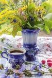 Blå drink för kopp kaffetecikoria med vasen, varm dryck, kaffeservise på broderad tygbakgrund arkivbild