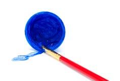 Blå färgmålarfärg i en krus och en borste Arkivbild