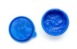 Blå färgmålarfärg i en krus på vit bakgrund Arkivbilder