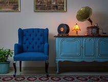 Blå fåtölj, tappningträljus - den blåa serveringsbordet, tände den antika tabelllampan, den gamla skivspelaregrammofonen och viny Royaltyfria Foton