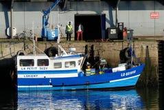 Blå fiskebåt tillsammans med hamnplatsen Arkivfoto