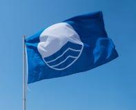 Blå flagga på stranden Royaltyfria Bilder