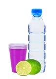 Blå flaska med vatten-, limefrukt- och plast-koppar som isoleras på vit Royaltyfria Bilder