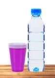Blå flaska med vatten- och plast-koppar på trätabellen Arkivfoto
