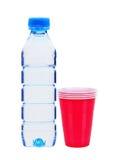 Blå flaska med vatten och röda plast- koppar Arkivfoto