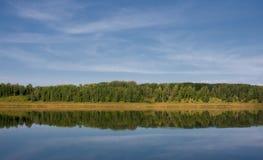Blå flod, reflekterad skog Arkivbild