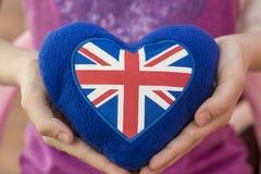 Blå flott hjärta med UK-flaggan i hans hand England är i dina händer Favorit- land för UK, Royaltyfri Foto