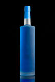 Blå flytande i en klar matte alkoholflaska Arkivfoton
