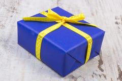 Blå gåva för jul eller annan beröm på träplanka Royaltyfri Bild