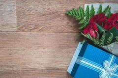 Blå gåvaask och en bukett av rosor Fotografering för Bildbyråer