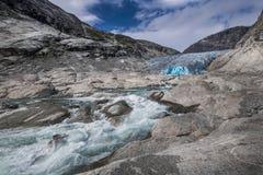 Blå glaciär med floden Nigardsbreen i Norge Arkivfoto
