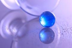 Blå glass boll på en glass tabell och en härlig abstrakt bakgrund Royaltyfri Fotografi