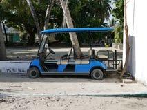 Blå golfvagn på en sandig strand i Maldiverna royaltyfri fotografi