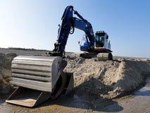 Blå grävskopa på högen av sand i lerig sand Royaltyfri Foto