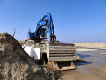 Blå grävskopa på högen av sand på konstruktionsplats Arkivfoton