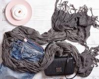 Blå grov bomullstvilljeans, svart handväska, grå halsduk, oxford läderkängor och platta med kakan Royaltyfri Fotografi