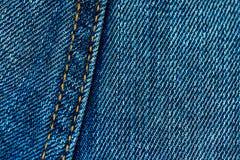 Blå grov bomullstvilljeansbakgrund med sömmen och orange trådhäftklammer Tillfälligt stads- klassiskt mode som anpassar bekläda b arkivfoto