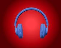 Blå hörlurar på röd bakgrund Royaltyfria Foton