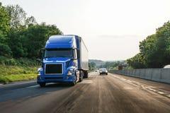 Blå halv-lastbil för 18 person som drar en skottkärra på huvudvägen med rörelsesuddighet royaltyfria foton