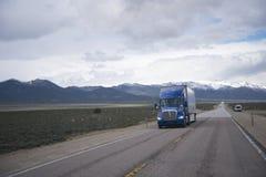 Blå halv lastbil på den raka vägen på den Nevada platån Arkivbild