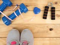 Blå hantel och mått och skosport på träbakgrund w Royaltyfri Foto