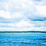 Blå havsframdel, molnig himmel, Sandy Beach och stad på Backgrouen Arkivbild