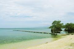 Blå havssandstrand med träpirlandskap Romantisk tonat foto för sjösida sikt Fotografering för Bildbyråer