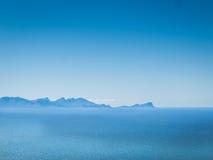 Blå himmel, blått hav och i avståndet, blåa berg Arkivbilder