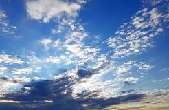 Blå himmel för superb afton med spridda moln på horisonten royaltyfria bilder