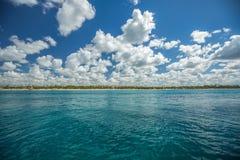 Blå himmel för vita fluffiga moln ovanför en yttersida av havet Royaltyfri Bild