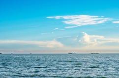 Blå himmel för vita fluffiga moln ovanför en yttersida av havet och fartyget Arkivbilder