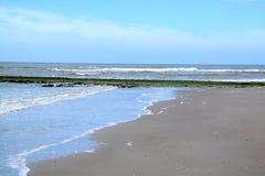 Blå himmel, hav, vågor och sandig kustlinje Arkivfoton