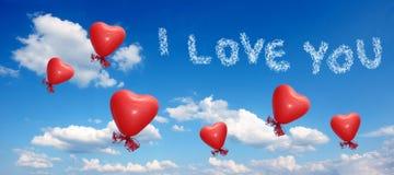 Blå himmel med ballonghjärtor och älskar dig meddelandet Arkivfoton