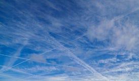 Blå himmel med contrails och moln arkivfoton