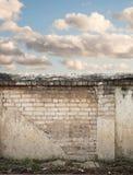Blå himmel med moln bak den spruckna väggen Arkivfoton