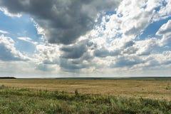 Blå himmel med moln, dalen med visset gräs och gräsplanvegetation, molnig dag för sommar, naturlandskap royaltyfria bilder