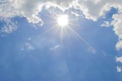 Blå himmel med moln och solen Arkivbild