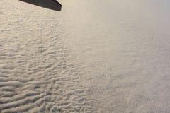Blå himmel med moln under vingen av ett flygplan fotografering för bildbyråer