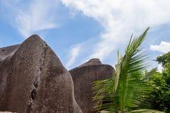 Blå himmel med något fördunklar och stora stenar framme arkivfoto