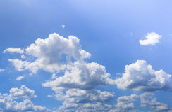 Blå himmel med pösig vit fördunklar i ljus klar solig dag Fotografering för Bildbyråer