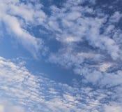 Blå himmel med pösiga vitmoln och en halvmåne Royaltyfri Foto