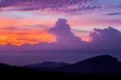 Blå himmel med purpurfärgade moln. Arkivbild