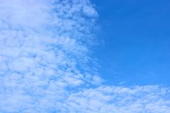 Blå himmel med spridda moln som flyttar sig med vinden Arkivfoto