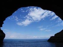 Blå himmel med vit fördunklar över havs- och grottakontur arkivbilder