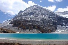 Blå himmel med vit fördunklar över sjön och snöberget Fotografering för Bildbyråer